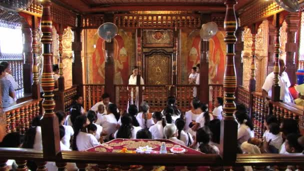 People with babies gather in the Temple of Tooth (Dalada Maligava) in Kandy, Sri Lanka