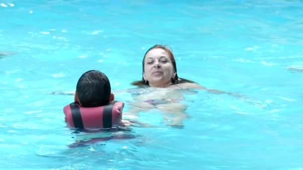 Mother With Her Son Swim in the Pool in Slow Motion.