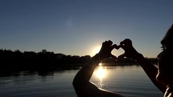 Ruce ukazují srdce při západu slunce v pomalém pohybu.