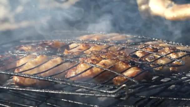 Vaření kuřecí křídla a stehna na dřevěném uhlí venku.