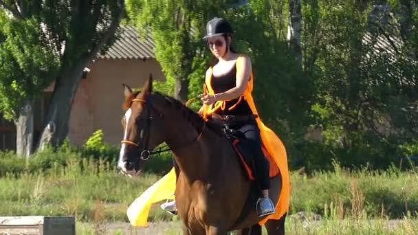 Dívka v helmu a brýle, jízda na koni. Zpomalený pohyb.