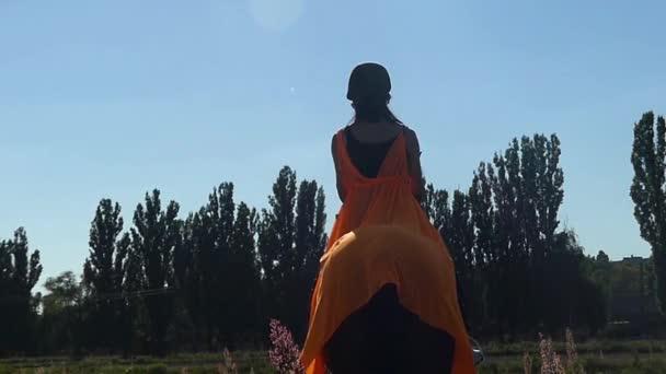 a lány a narancssárga kalap és a köpenyét, lovaglási lehetőség a lassú mozgás.