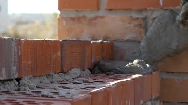 Rukou tvůrce dal cementové malty. Ruka je zdivo z cihel.
