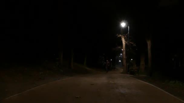 eine einsame junge Frau, die auf einer nächtlichen Straße spaziert.