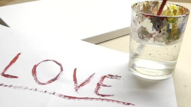 szerelem-írta a papír és egy kéz, egy lapos tipp ecset az egy pohár víz tisztítása