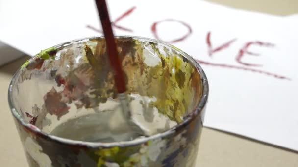 Egy lapos tipp ecset be egy üveg a víz a love felirattal közeli dunking
