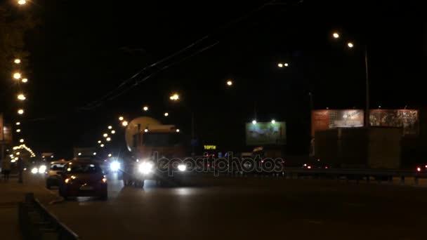 Schwere Lastwagen und Autos bewegen sich langsam auf einer nächtlichen Stadtautobahn in Osteuropa.