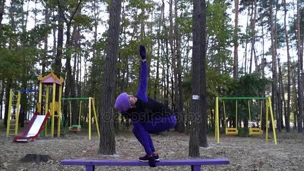 Krásná mladá žena dělá jógu, cvičení s zvedl ruce v podřepu stoje na lavičce