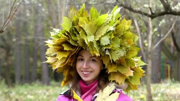 Girl in the Forest Smiles and Shakes Her Hand With Wreath of Yellow Leaves on Her Head.