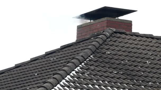 Původní komín s kouř stoupající z něj na střeše zahrnuty s černá dlaždice v zimě