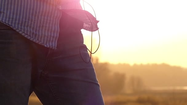 Young Man is Standing With Earbuds in Ears and a Player in Hands With the Sunny Rays Beaming From Behind in the Early Spring in Slo-Mo
