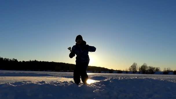 Kisfiú ünnepli egy kis győzelem, és beugrott az ég, a csésze, a kezében, lassítva a naplemente.