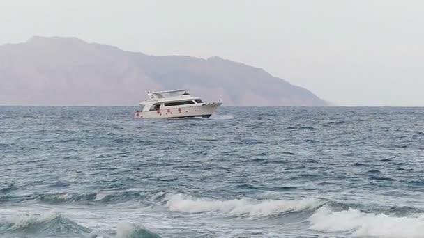 Bílé malé lodi plave přes bouřlivé moře v pomalém pohybu.