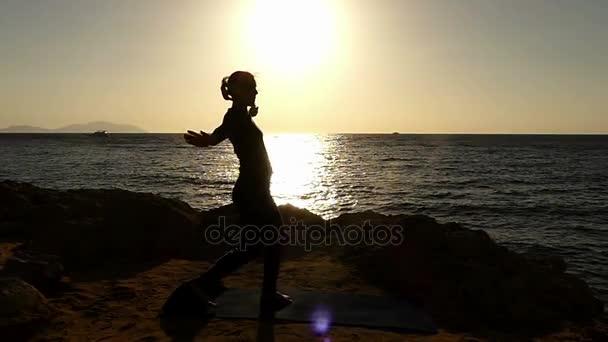 Dívka dělat Kung-fu kop v pomalém pohybu při západu slunce na pláži