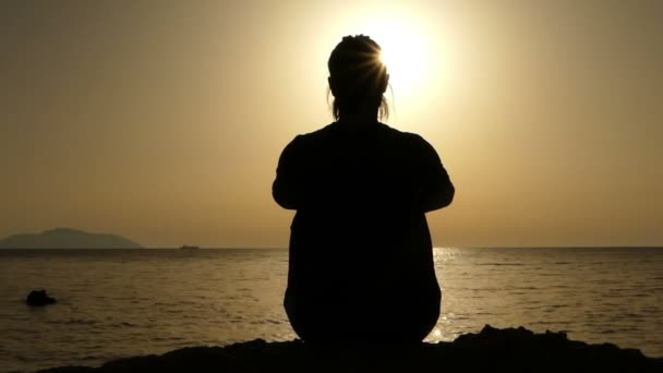 Sportive Young Woman is Sitting, Turning Her Head at a Nice Sunset on the Stony Sea Coast of the Red Sea.