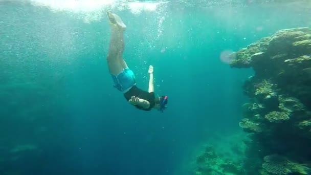 Uomo provare immersioni subacquee vicino alla barriera corallina al rallentatore.