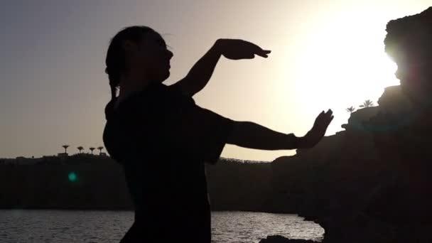 Lustigen Tanz des Mädchens Silhouette bei Sonnenuntergang.