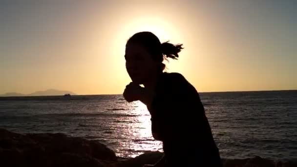 Žena box za úsvitu na pozadí moře