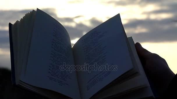 Ruce drží otevřenou knihu s básní pozadí soumraku oblohy s slunečního záření v pomalém pohybu