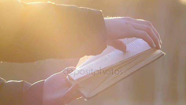 Krásně osvětlené rukou otočit stránky knihy při západu slunce na rozostřeného pozadí ve zpomaleném záběru