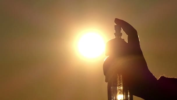 Person Sprays Liquid in the Bottle and Creates a Beautiful Cloud of Ions That Dissolve in the Air During Sunset