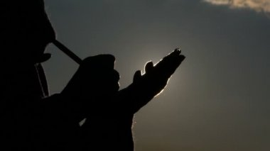 a Silhouette of a Person Writes in Notepad on the Background of the Sky, the Silhouette of Her Hands is Visible, the Sun Creates a Beautiful Backlight