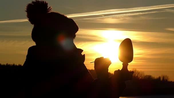 Silueta ženy drží že dřevěné vajíčko v ruce a s pomocí štětce maluje vzor krásné soumraku oblohy v pomalém pohybu.