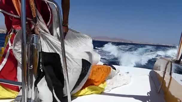 Zpěněná voda víru po pohybující motorový člun s mužem udržet padák v Rudém moři