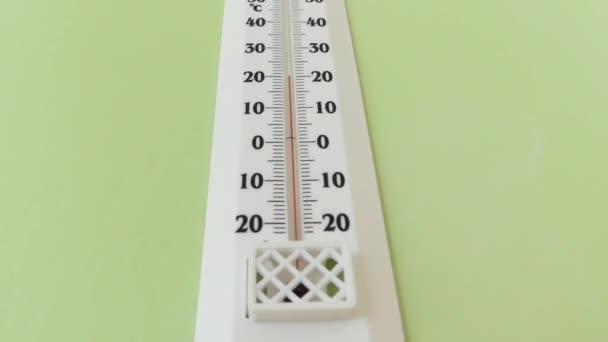 Fehér lóg a falon belül néhány épület és 20 találat hőmérő plusz
