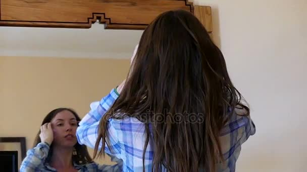 Beautiful Girl in a Shirt Puts Her Hair in Order Before a Mirror in Slo-Mo