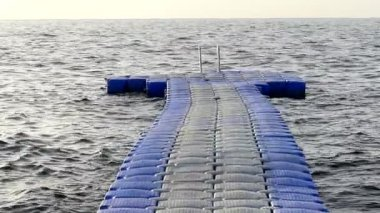 Blue and White Plastic Pontoon is Floating on the Red Sea Waves on a Sunny Day