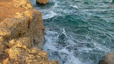 The Foamy Sea Waves Crashing the Light Brown Rocky Seacoast in Egypt in a Sunny Day