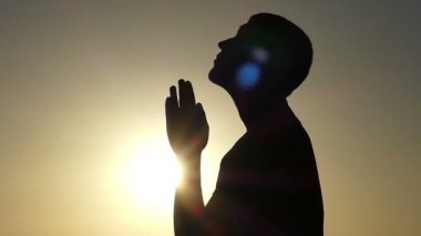 Young Man Stands in Profile and Prays in Christian Way at Sunset in Slo-Mo