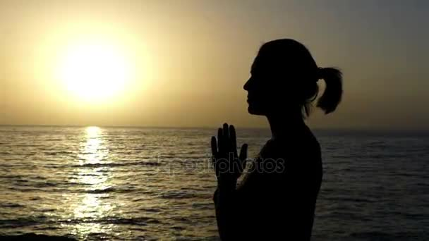 Štíhlá žena se modlí v Christian tradici na mořskou pláž při západu slunce v létě