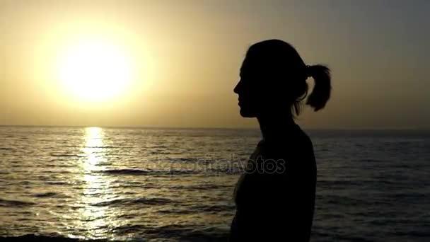 Mladá žena protíná v Christian tradici na mořskou pláž při západu slunce v létě