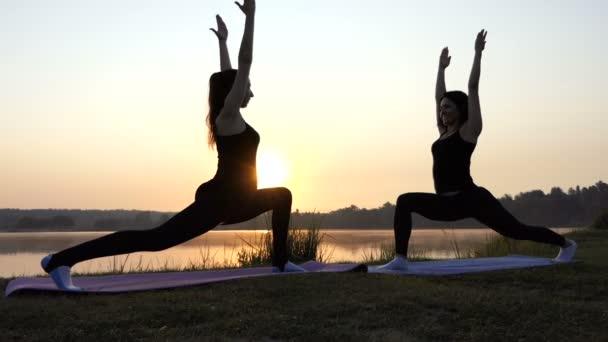 Dvě štíhlé ženy dělat Warrior cvičení jógy při západu slunce na pobřeží jezera v Slo-Mo