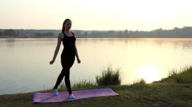 Sportive Pregnant Girl Stands on a Mat and Raises Her Knee at Sunset