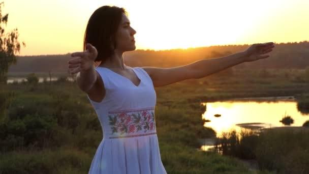 eine junge schlanke Frau macht bei Sonnenuntergang Ballettbewegungen mit ihren Händen