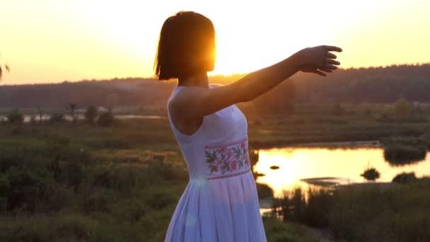 eine junge schlanke Frau macht Ballettbewegungen mit ihren Händen bei Sonnenuntergang im Slo-mo