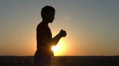Small Boy Trans His Wrists on a Lake Bank at Sunset