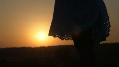 Female Legs and a Folk Dress Hem Waving Both Sides at Sunset