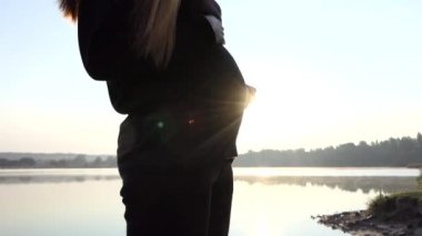Female Hands Gok With Baby`s Slippers on Pregnant Belly at Sunset