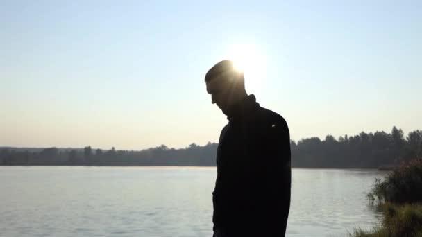 Fiatal apa nézi a Romper öltönyt a baba, a tó partján, a csodálatos naplemente