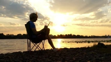 Bright Man Sits on a Riverbank, Reads His Notes in the Rays of a Sunset in 4k