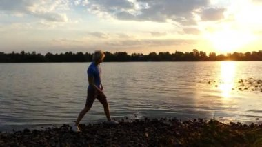 Bright Sunset and a Boy Throwing Flat Stone in the River Water in 4k