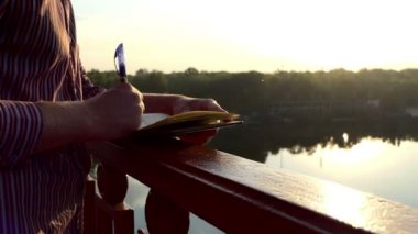 Young Man Comes up With Ideas, Puts Them Down in a Notepad on a Bridge in Slo-Mo