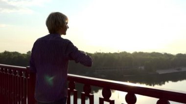 Young Man Snaps Fingers on a Modern Bridge at Sunset in Summer in Slow Motion