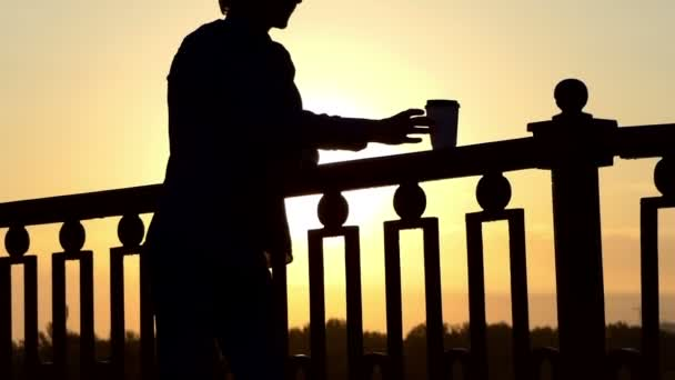 Blond Man Drinks Coffee From a Paper Cup and Enjoys a Sunset on a Bridge in Slo-Mo