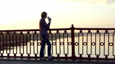 Romantic Man Drinks Coffee From a Paper Cup and Enjoys a Sunset on a Bridge in Slo-Mo