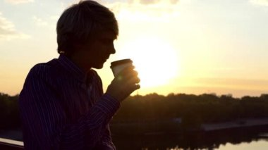 Young Man Drinks Coffee From a Paper Cup and Enjoys a Sunset on a Bridge in Slo-Mo